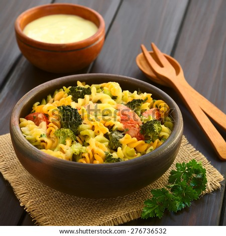 Baked fusilli pasta and vegetable (broccoli, tomato) casserole in rustic bowl, wooden cutlery, cream sauce in back, photographed with natural light (Selective Focus, Focus in the middle of the dish) - stock photo
