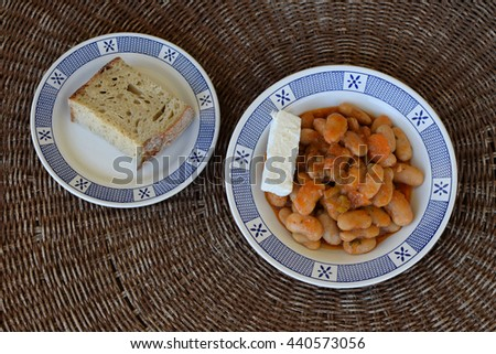 Baked giant beans gigantes with feta cheese and bread. Greek food. - stock photo