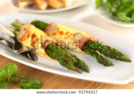 Baked green asparagus wrapped in bacon and wonton dough (Selective Focus, Focus on the asparagus tips of the first bundle)
