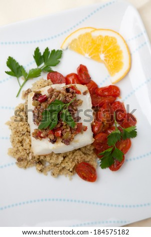 Baked halibut with olive tapenade crust garnished with couscous, fried cherry tomatoes, and fresh parsley.  - stock photo