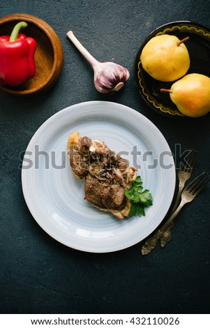 Baked  lamb meat with pepper on a blue plate over dark background, top view - stock photo