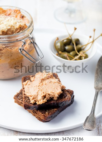 Baked meat pate in jar and on bread Delicious sandwich Gourmet food - stock photo