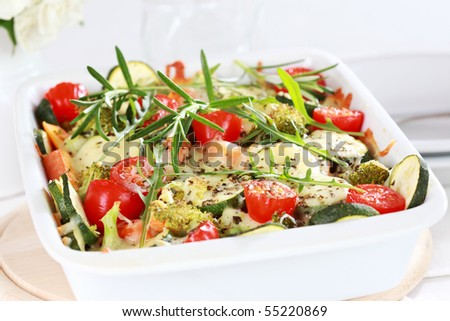 Baked mixed vegetable with cheese and herbs - stock photo