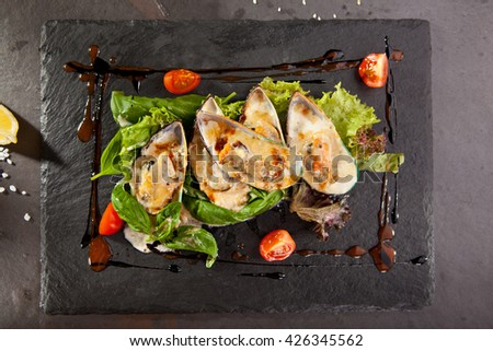 Baked Mussels with Spicy Sauce. Garnished with Cherry Tomato and Salad Leaves - stock photo