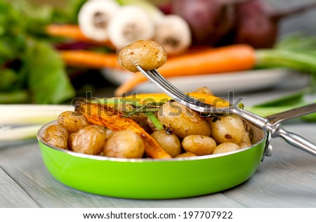 Baked new potatoes and carrots with garlic in frying pan against vegetable background - stock photo