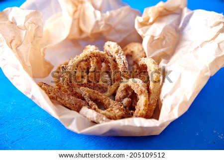 Baked onions rings served on baking paper - healthy dish for friends party. - stock photo