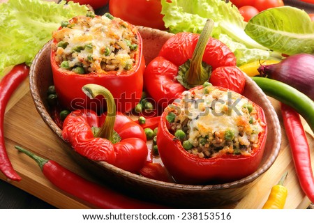 Baked peppers stuffed with meat rice and vegetables on cutting board - stock photo
