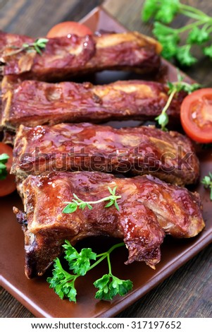 Baked pork ribs on plate, shallow depth of field - stock photo