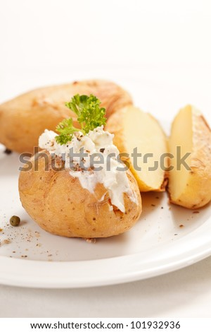 Baked potato filled with soft cheese - stock photo