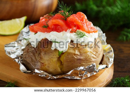 Baked potato with cream of the cream cheese and salted salmon, closeup. - stock photo