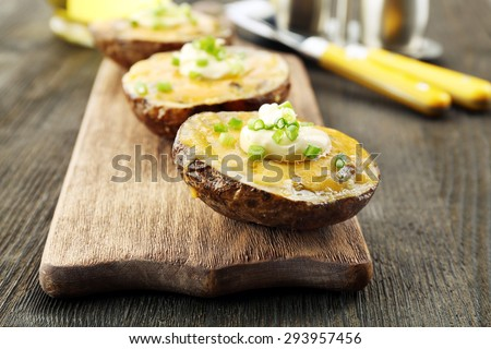 Baked potato with mayonnaise and chives on wooden cutting board, closeup - stock photo