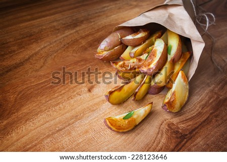 Baked potato with rosemary  in a cone of paper  - stock photo
