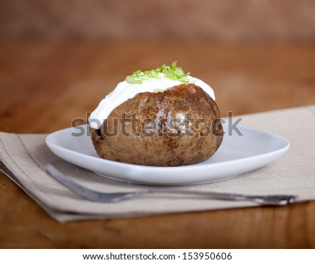 Baked potato with scallions on plate - stock photo