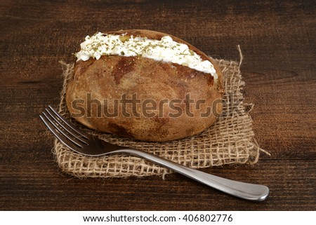 baked potato with sour cream and ground chives - stock photo