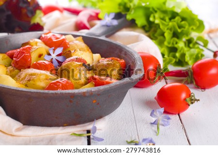 Baked potatoes  and tomatoes on  Wooden background.