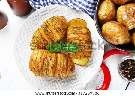 Baked potatoes on wooden table, closeup - stock photo