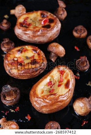 Baked potatoes with mushrooms and spices on pan close up - stock photo
