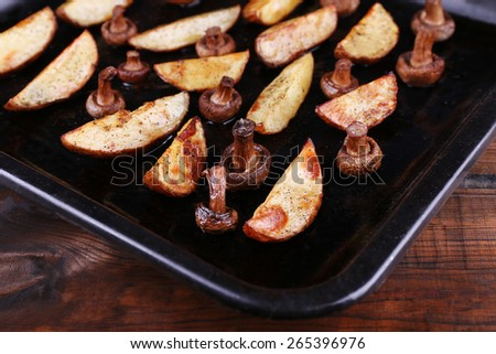 Baked potatoes with mushrooms and spices on pan on table close up - stock photo