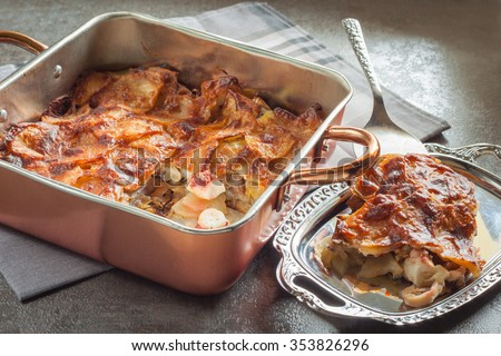 Baked potatoes with octopus and eggplant  in a copper pan on a gray background, horizontal - stock photo