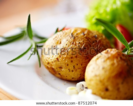 Baked potatoes with rosemary on a plate - stock photo