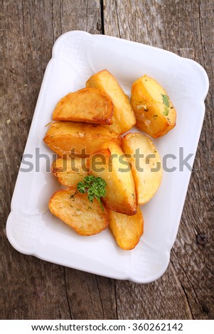 baked potatoes with spices in white bowl on an old wooden background