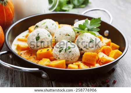 Baked pumpkin and chicken meatballs with herbs in a saucepan