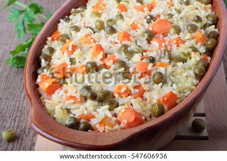 Baked rice with peas and sliced carrot in ceramic dish