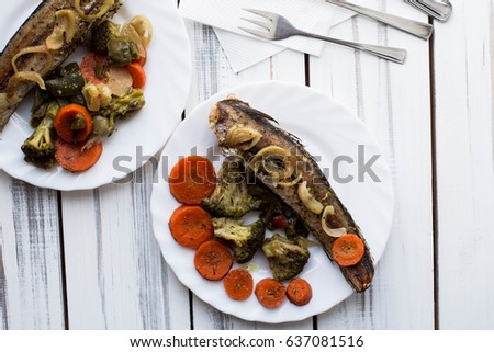 Baked roasted fried fish with baked, baked, gifted vegetables on a white wooden table