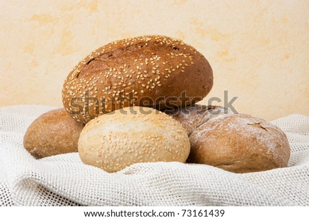 baked rolls and bread on table napkin - stock photo