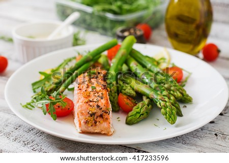 Baked salmon garnished with asparagus and tomatoes with herbs - stock photo