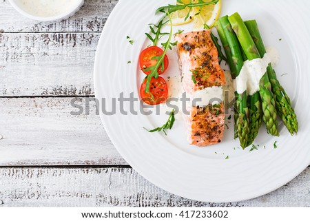 Baked salmon garnished with asparagus and tomatoes with herbs. Top view - stock photo