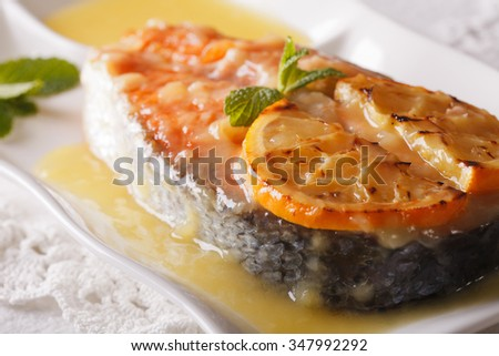 baked salmon steak with orange sauce and mint on a plate close-up. horizontal