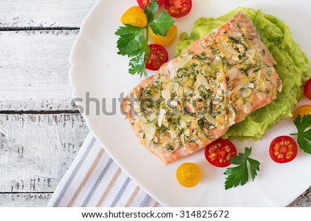 Baked salmon with cheese and almond crust and garnished with mashed potatoes and green peas. Top view - stock photo