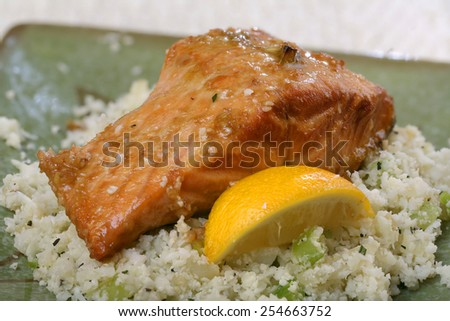 Baked Salmon with lemon wedge and rice cauliflower side dish - stock photo