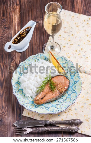 Baked salmon with rice garnish. Plate with grilled salmon, rice, lemon and a glass of wine on the table. Lunch / dinner. - stock photo