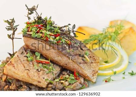 Baked salvenius filet on lentil salad - stock photo