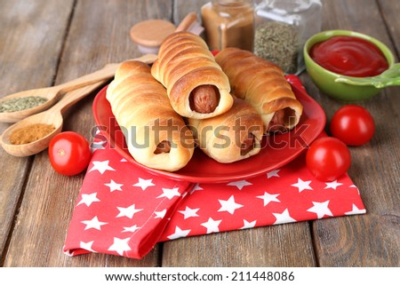 Baked sausage rolls on plate on table close-up - stock photo