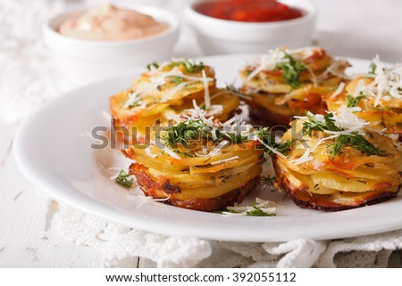 Baked sliced potatoes with Parmesan close-up on a plate on the table. horizontal