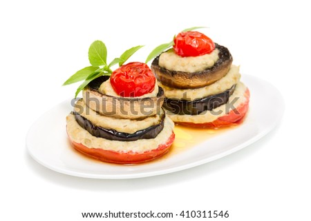 baked slices of eggplant, mushrooms and tomatoes with aubergine puree with cream sauce, isolated on white