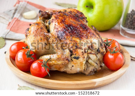 Baked small chicken with a ruddy crust, stuffed with apples on the wooden plate, Christmas food - stock photo