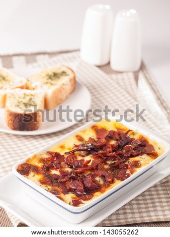 baked spinach with cheese bacon topping  and garlic bread