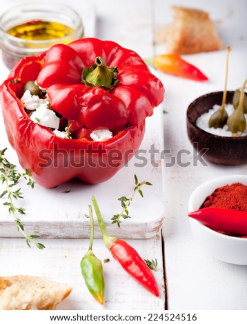 Baked stuffed bell peppers filled with  cheese, tomatoes, herbs, capers and anchovies on a white wooden background - stock photo