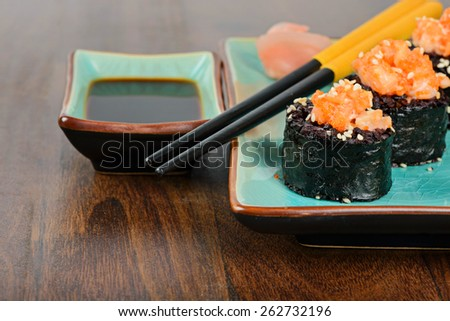 Baked sushi rolls with black rice and salmon, served on blue plate with pickled ginger, soy sauce and black chopsticks. - stock photo