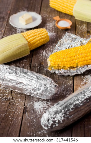 baked sweet corn on rustic wooden table - stock photo