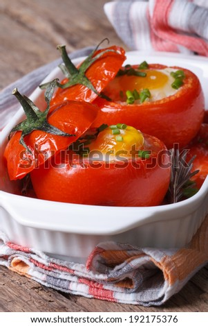 Baked tomatoes stuffed with eggs close-up on the table. vertical