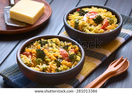 Baked tricolor fusilli pasta and vegetable (broccoli, tomato) casserole in rustic bowls, wooden cutlery on side, photographed with natural light (Selective Focus, Focus in the middle of first dish) - stock photo