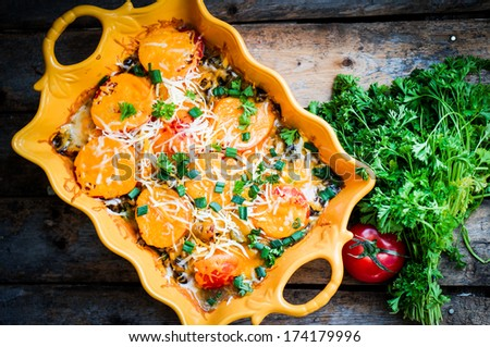 Baked vegetables in a dish on wooden background - stock photo