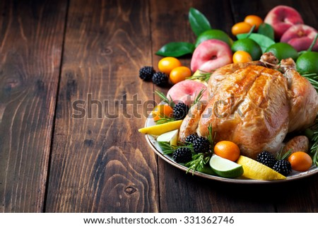 Baked whole chicken, fresh fruit and berries, selective focus - stock photo