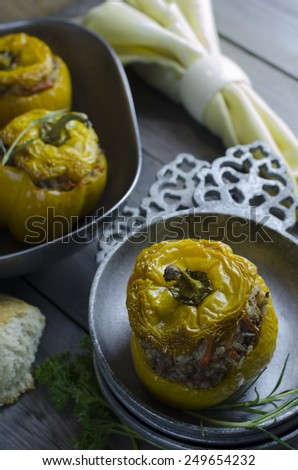 Baked yellow peppers stuffed with meat and rice in rustic metal bowl - stock photo