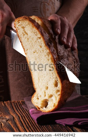 Baker cutting and holding fresh made bread  isolated on white background. Baker and bakery, rustic styles.  - stock photo